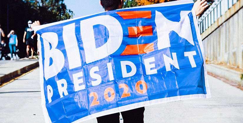 Man holds 'Biden President 2020' flag across his back | Readable, free readability test